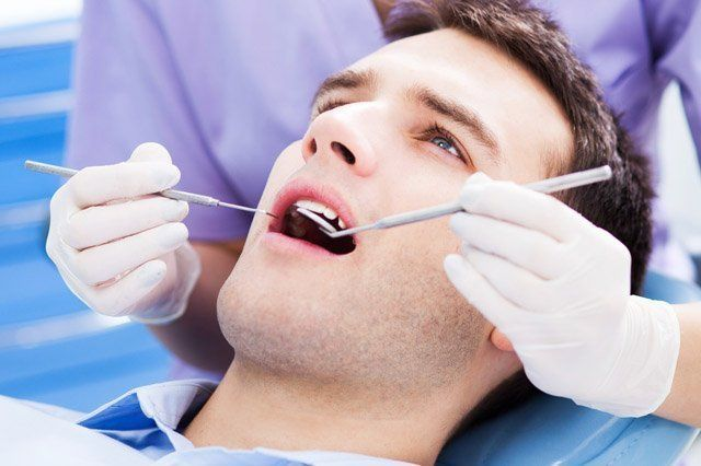 dentist looking in male patients mouth
