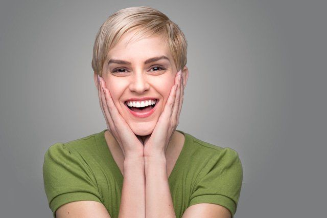 smiling woman with hands on face in green top