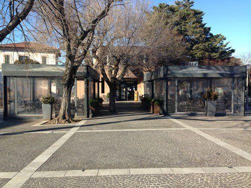 vista di una piazza con alberi spogli due verande e in lontananza un pino