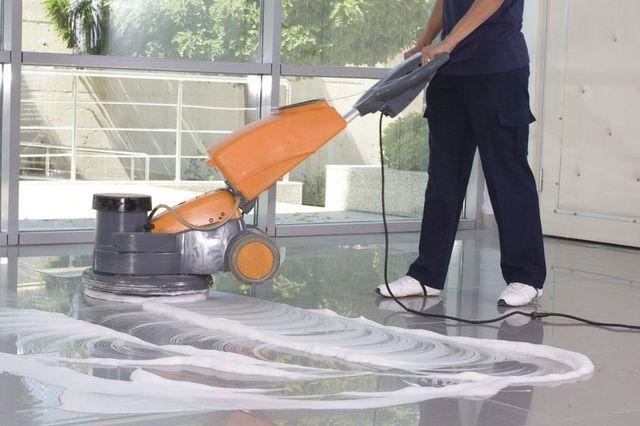 operaio utilizza una monospazzola sul pavimento