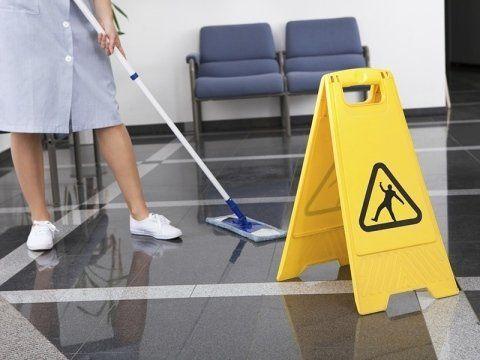 donna pulisce il pavimento con un mocio in microfibra