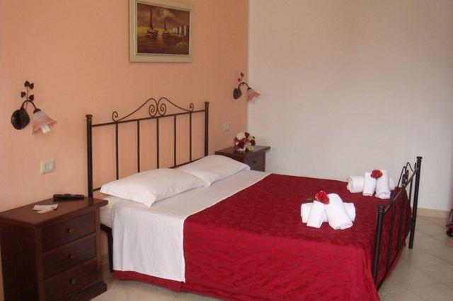 Vista di una camera da letto pronta per gli ospiti, con lenzuola rosse ed asciugamani disposti con cura.