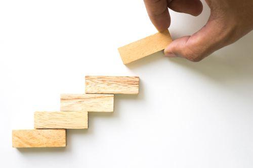 Una mano che crea una scala con dei mattoncini in legno