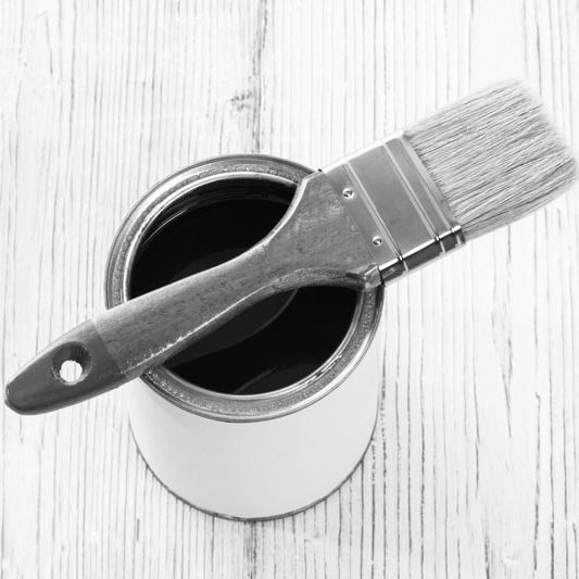 Black and white image of a paint can and paint brush.