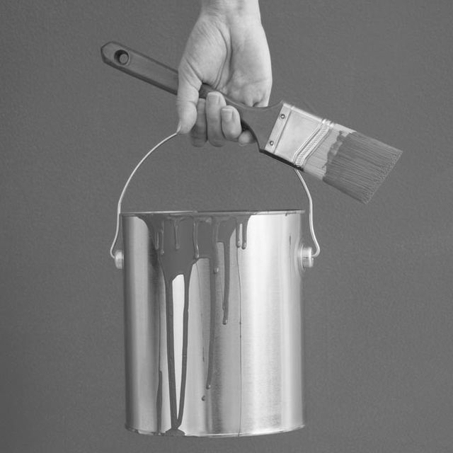 Black and white image of a person holding a paint brush and a paint can.