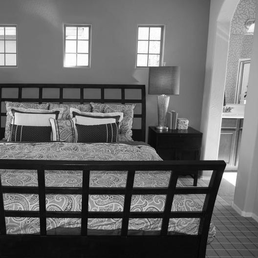 Black and white image of a bedroom.