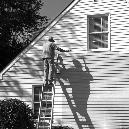 Black and white image of a man on a ladder painting the exterior of a house.