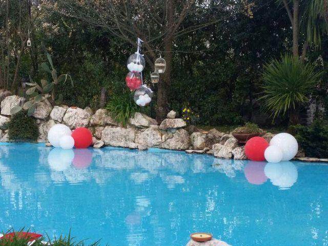 una piscina con delle palle colorate e ai bordi delle rocce