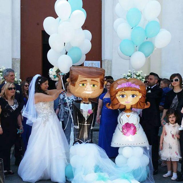 due palloncini a forma di sposi, gli sposi e gli invitati