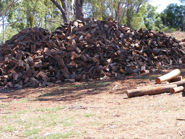 stack of cut wood under shade for drying