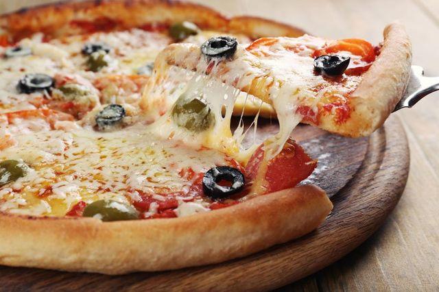 Un tagliere di una pizza con delle olive nere e formaggio