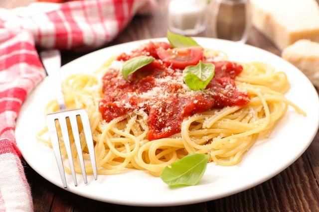 Un piatto di spaghetti con sugo e delle foglie di basilico