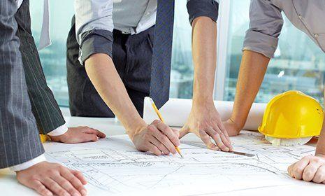 tre tecnici analizzano un progetto, uno lo modifica con una matita