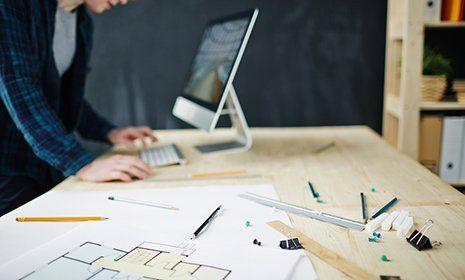 impiegata lavora al computer con progetto a fianco