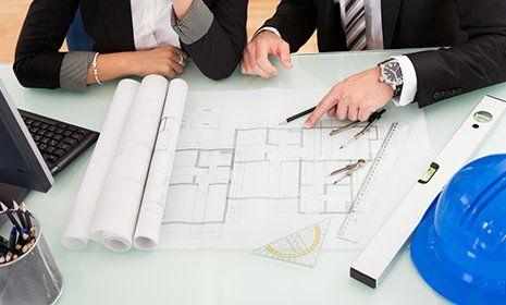 colleghi discutono un progetto il cui disegno è poggiato su un tavolo