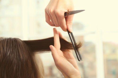una mano con una forbice, un pettine e un altra mano con i capelli di una donna