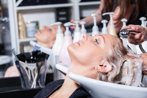 una mano mentre lava i capelli di una donna sdraiata