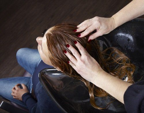 due mani mentre massaggiano la testa di una donna