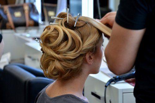 una mano di un parrucchiere mentre fa una piega ad una donna con i capelli biondi