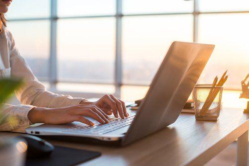 persona in ufficio scrive al computer portatile