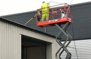 Man pressure cleaning factory roof