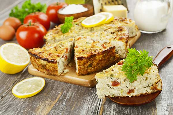 torta di pesce alle erbe su un tagliere, accanto limone,pomodori,uova e delle ciotole di legno