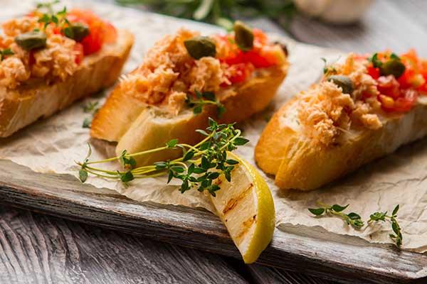tre bruschette con pesce pomodorini e capperi
