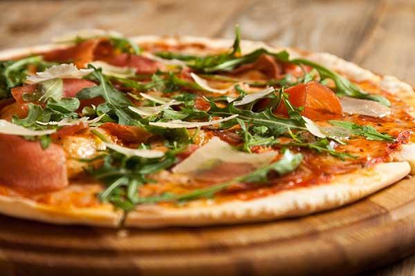 una pizza con rucola e prosciutto crudo di Parma su una tagliere vista da vicino
