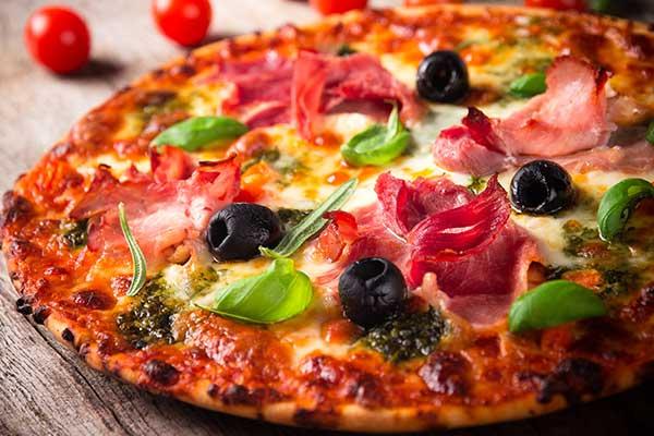 pizza con prosciutto cotto, olive nere e basilico, accanto dei pomodorini, il tutto su un tavolo di legno
