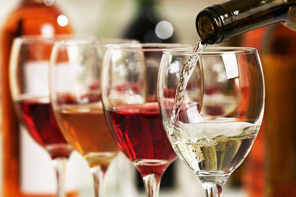 due bicchieri di vino rosso, uno di bianco e una bottiglia che sta versando dell'altro vino bianco in un bicchiere