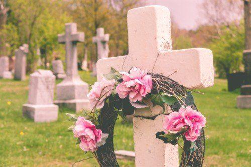lapide a forma di croce con corona di fiori