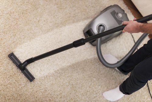 persona mentre utilizza un aspirapolvere su un tappeto