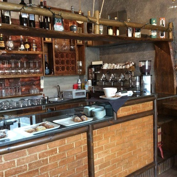 il bar visto da vicino con vetrina e brioches, macchina del caffe' e calici sugli scaffali