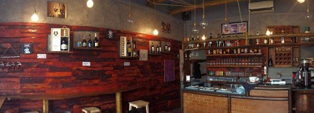 insegna con scritta calice e caffe' con vista del bar in mattoni arancioni e bottiglie esposte
