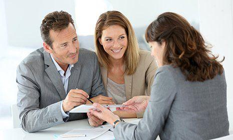 Una coppia di mezza età si consulta con un impiegato d'azienda