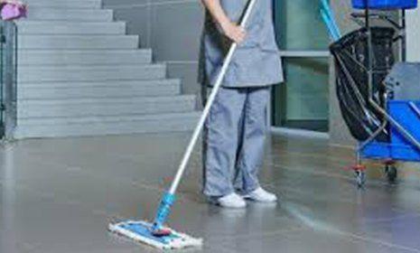Impiegato che pulisce un pavimento