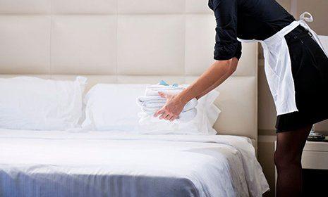 Donna che poggia degli asciugamani su di un letto d'albergo