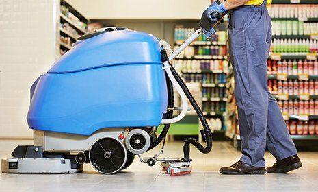 Impiegato che lucida il pavimento di un supermercato con il macchinario apposito