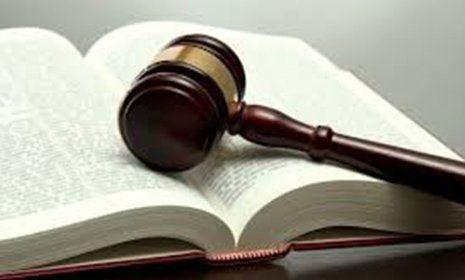 Un volume con un martello da giudice poggiato sopra