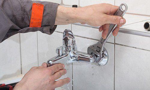 Un idraulico mentre stringe un bullone di un rubinetto