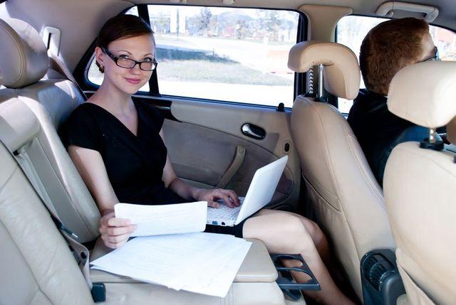 una donna sorridente seduta in macchina con un pc portatile
