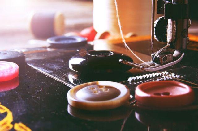 close up di bottoni e ago da macchina per cucire