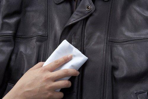 una mano che pulisce un giubbotto di pelle nero