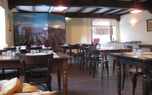 Vista del ristorante, al fondo un grande pannello con la foto di vigneti