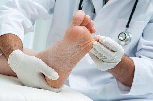 medico che tira il mignolo del piede a un paziente