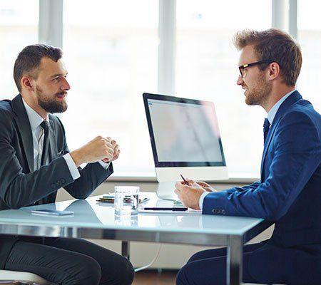 due uomini alla scrivania che parlano