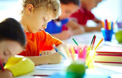 Portrait of boy drawing at playschool in MO