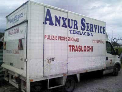 un camion dei traslochi di color bianco e una scritta ANXUR SERVICE TERRACINA sul rimorchio