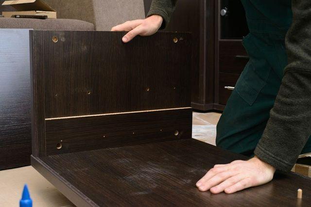 un uomo sta assemblando un'asse di legno scuro