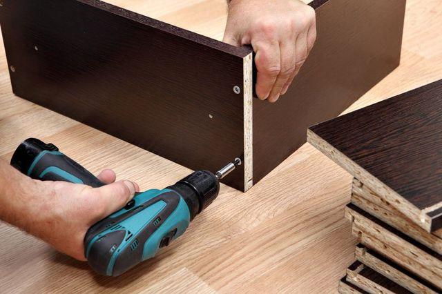 la mano di un uomo con un trapano avvitatore al lavoro su delle assi di legno